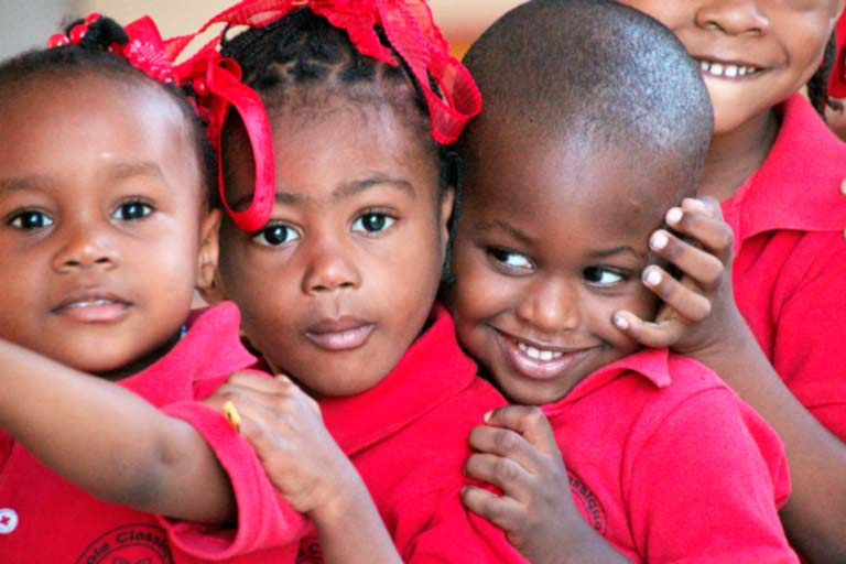 Niños haitianos con polo rojo aguardan a la entrada de la clase