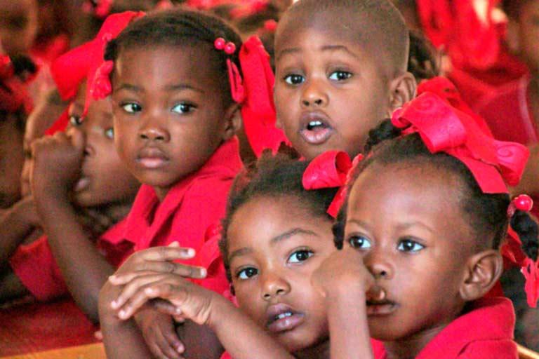 Niños haitianos atienden a su profesor