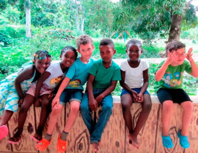 Niños haitianos y europeos sentados posando a la hora del recreo