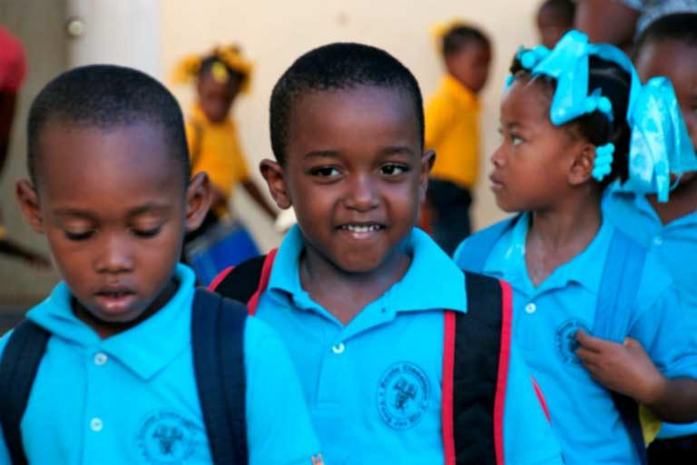 Niños haitianos con polo azul yendo a clase con sus mochilas