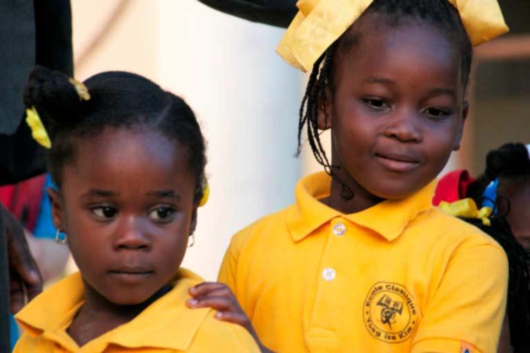 Niñas haitianas con polo amarillo a la entrada de la escuela