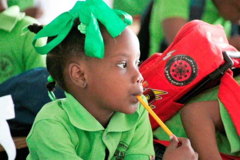 Niña haitiana con polo verde atiende en clase