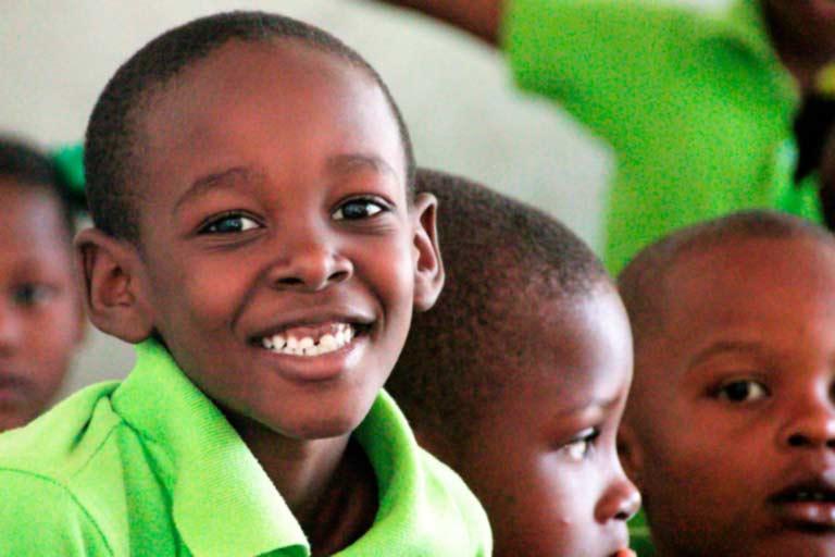 Niño haitiano con polo verde sonríe a la cámara
