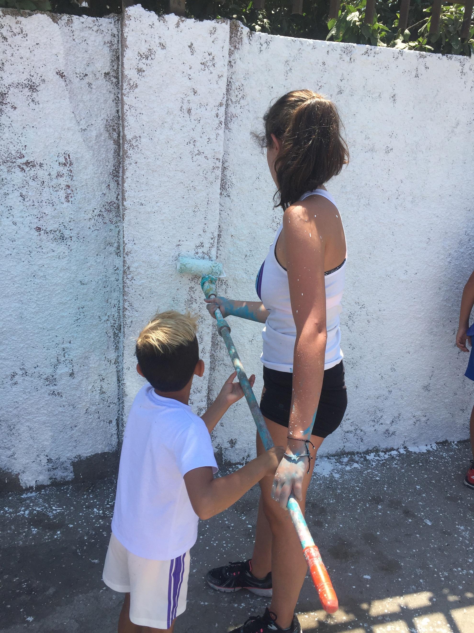 Una chica con un niño pintan una pared de blanco